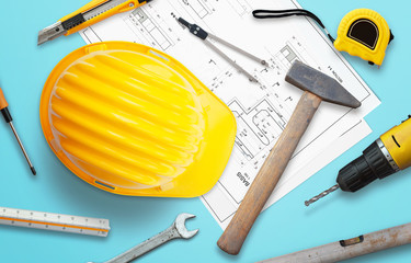 Construction tools and project drawings on table. Top view.