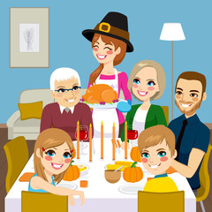 Happy family having thanksgiving dinner together with mom serving traditional roasted turkey