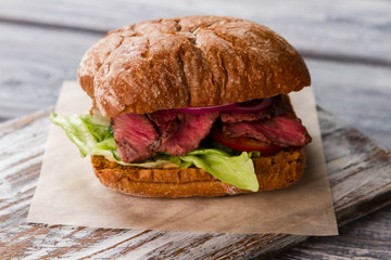 Sandwich on gray wooden board. Slices of meat and lettuce. Homemade sandwich with veal. Your meal is waiting.