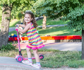 outdor portrait of young smiling girl riding scooter in a summer