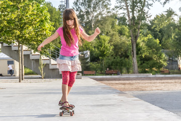 outdoor portrait of young smiling teenager girl riding skateboar