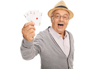 Elderly man showing four aces