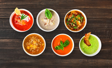 Variety of soups at brown wood, top view