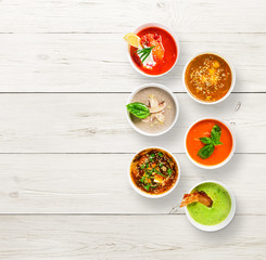 Variety of soups at white wood, top view, copy space