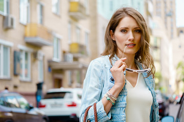Fashionable brunette woman standing on city street