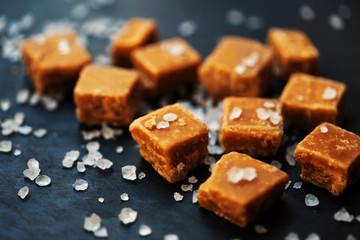 Caramel candies. Salted caramel pieces and sea salt macro.