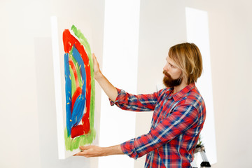 Young male artist standing with a picture