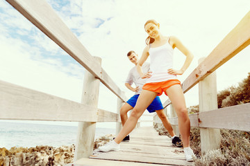 Runners. Young couple exercising on beach