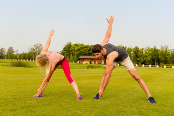 Sportive young couple doing exercises in the park to be fit