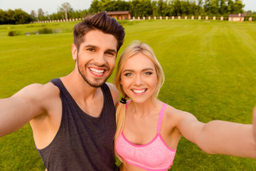 Athletic healthy cheerful couple making selfie after training