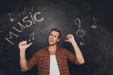 Cheerful happy musician dancing on the background of blackboard