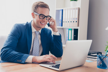 Smart smiling businessman talking on phone and typing on laptop