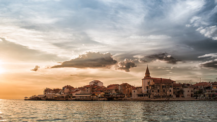 The coast and the promontory of Umag Croatia at sunset with stormy sky