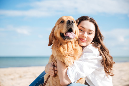 Tender smiling young woman hugging her dog on the beach