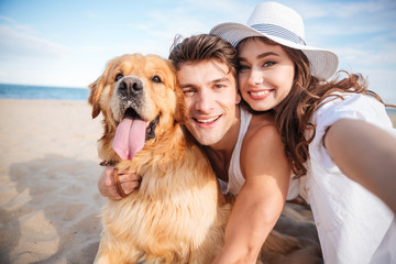 Happy couple hugging their dog and smiling on the beach