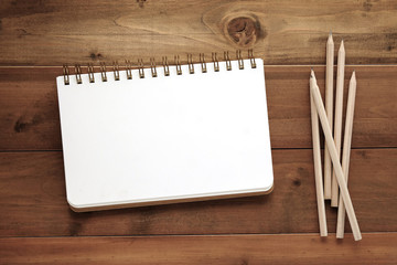 Blank note book and pencils on wood background
