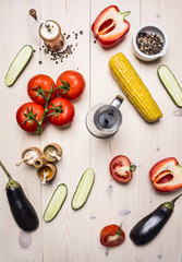 Ingredients for cooking vegetarian salad with tomatoes, whole pepper, red bell pepper, corn, cucumbers and seasonings  on wooden rustic background top view close up