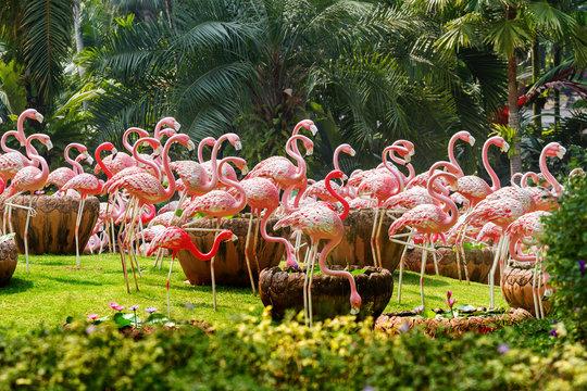 Flock of pink flamingos. Garden scultures in the Nong Nooch garden. Decorative statues of large exotic birds. Pattaya, Thailand.
