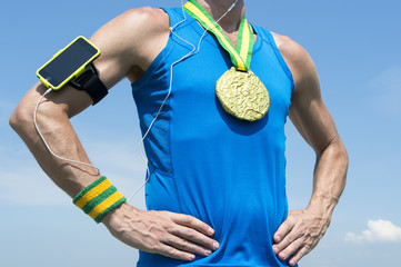 Gold medal athlete standing with mobile phone armband and headphones against blue sky