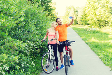 couple with bicycle and smartphone taking selfie