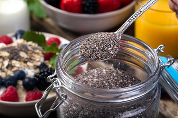 Spoon of chia. Bowl with berries.