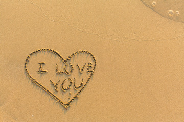 Inscription I Love You inside a Heart hand-painted on fine golden beach sand.