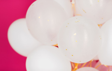 close up of white helium balloons over pink