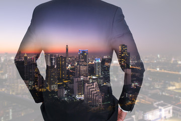 Double exposure of business man Back, looking ahead and night city as vision of leader concept.