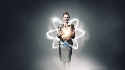 Woman scientist presenting atom research concept . Mixed media
