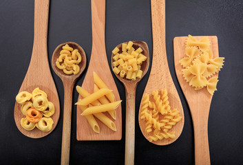 Various shapes of pasta on a black background