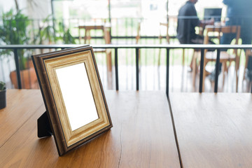 Vintage photo frame on wooden table.