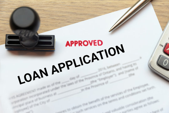 Approved loan application form lay down on wooden desk
