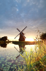 gold sunshine behind Dutch windmill by river