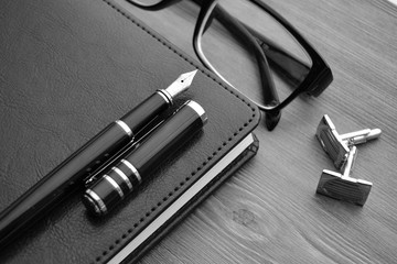 Business accessories on desktop: notebook, diary, fountain pen, cufflinks, glasses.