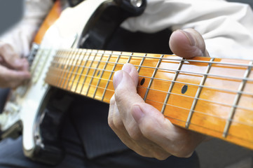 Elderly musician playing electric guitar.