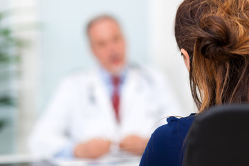 Doctor talking to her patient in her office