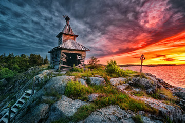 Wooden old church by the enchanting sunset sky