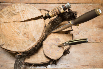 Hunting knives thrust in stumps on a wooden background