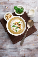 Champignon cream soup with fried mushrooms and fresh herbs on rustic white wooden table, top view
