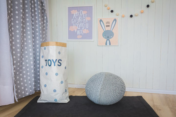 Two nice pictures, bag for toys and bear on the pouf in children's bedroom
