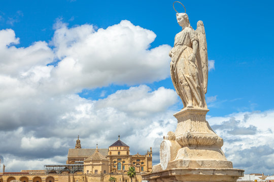 San Rafael Archangel statue on the popular Roman Bridge in Cordoba with behind the Cathedral of the Andalusian city, Spain.