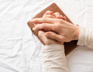 High angle view of middle aged woman's hands clasped over brown leather bound journal on white tablecloth