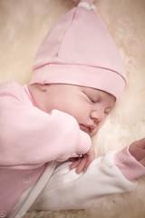 newborn girl in a pink dress sleeping on sheep skin