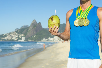 Champion athlete wearing gold medals celebrating with coconut on Ipanema Beach in Rio de Janeiro, Brazil