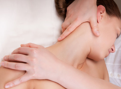 Therapist doing massage on a woman's neck by extending neck muscles