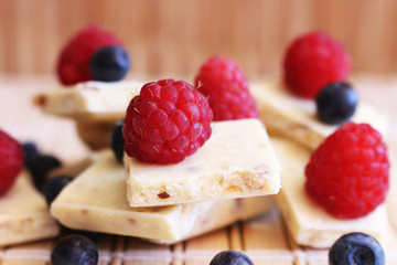 White chocolate stack a lot of pieces with fresh raspberries berries and blueberries on wooden background