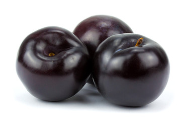three black plums, isolated on white background