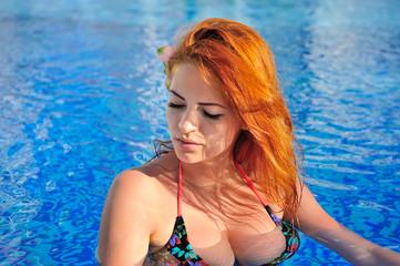 Beautiful young woman in bikini in blue water pool