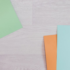 Flat lay set: pieces of paper in different colors on wooden floor. Top view. Minimal concept.