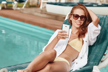 Happy smartphone woman relaxing near swimming pool listening wit